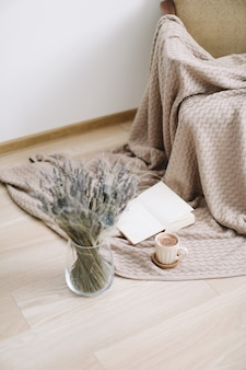 Cup of coffee, a book and flowers on wooden background. top view. flatlay. cozy home