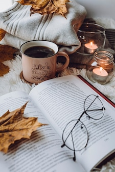 A cup of coffee, a book on a white blanket, candles, glasses.