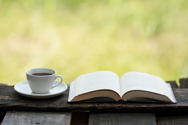 Cup of coffee and a book on a wooden table.