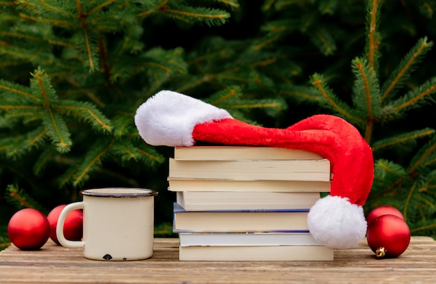 Cup of coffee and books with santa claus hat on wooden table