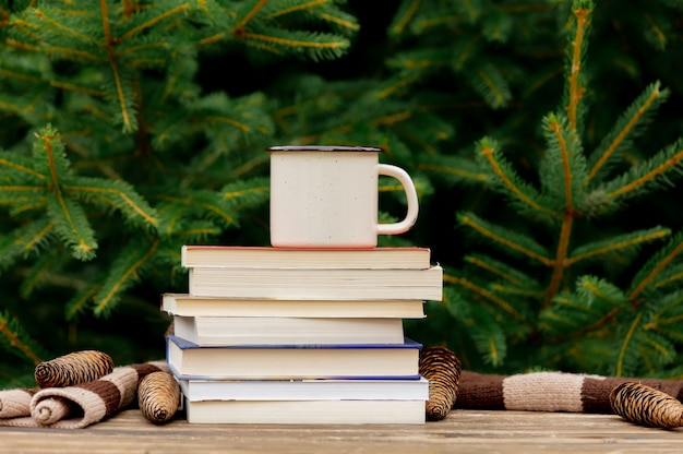Cup of coffee and books on wooden table with spruce branches on background