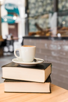 Cup of coffee over books on wooden table