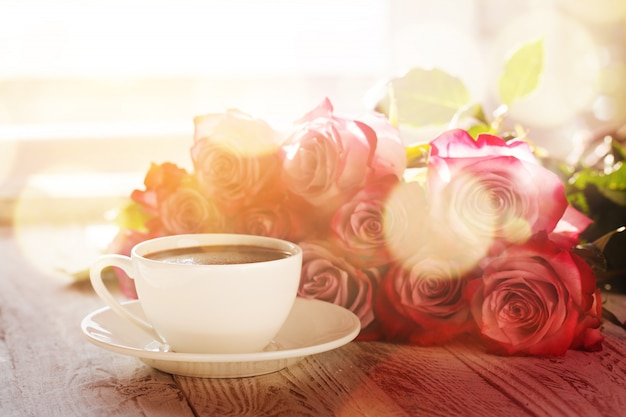 Cup of coffee and bouquet pink roses on table