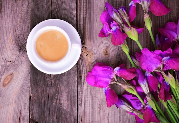 Cup of coffee and a bouquet of purple irises on a gray wooden surface