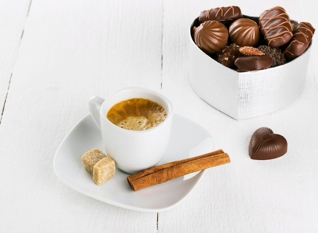 Cup of coffee and box of chocolates on a white wooden background