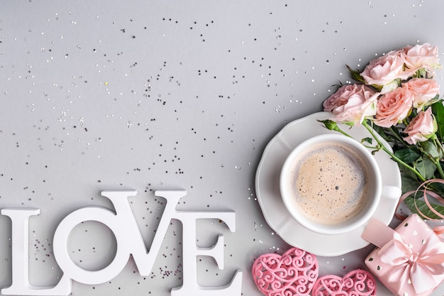 Cup of coffee, box with a gift and pink roses on a festive gray