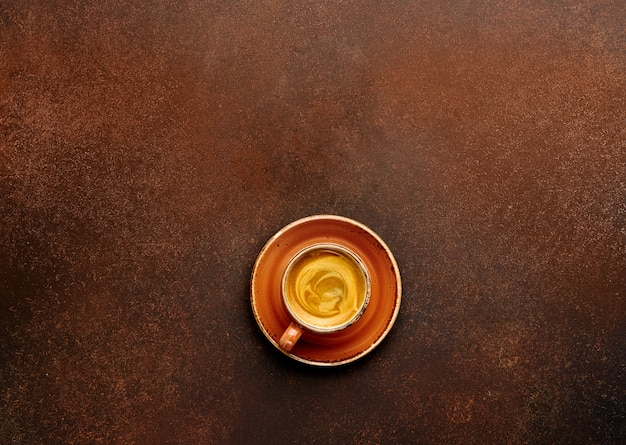 Cup of coffee on brown background with empty place for your text or lettering.