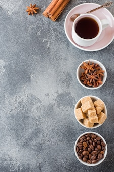 Cup of coffee, brown sugar and cinnamon with anise on concrete background.