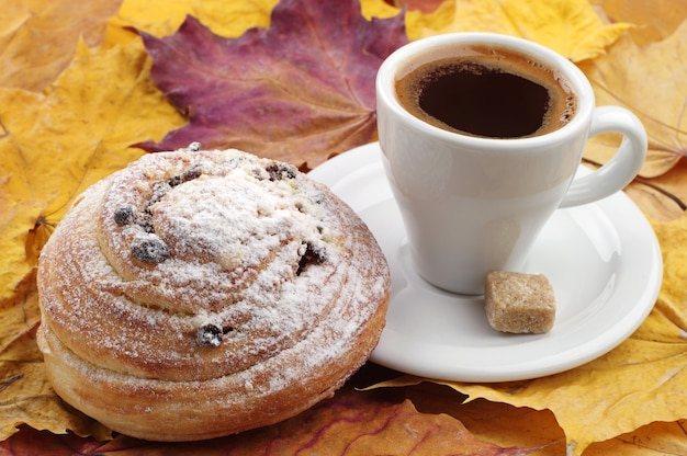 Cup of coffee and bun with raisins on autumn leaves