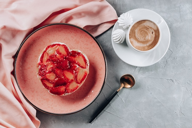 Cup of coffee and cake with strawberries on gray table