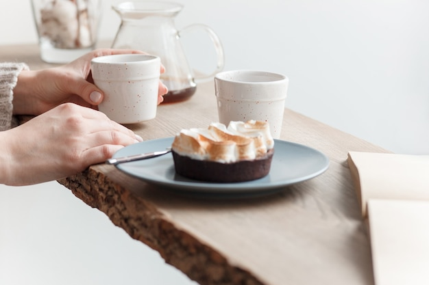 Cup of coffee, cake, wooden windowsill. in the background white window. barista, cafe, making coffee, preparation and service concept.