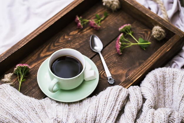 Cup of coffee and candle on rustic wooden serving tray and knitting warm woolen sweater