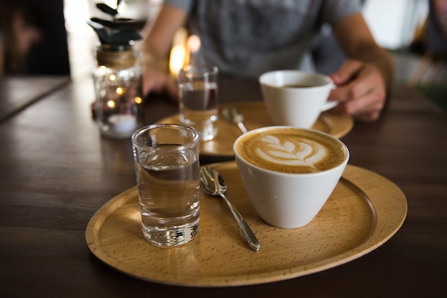 Cup of coffee cappuccino and a glass of water on a wooden tray. a man holding serving cup of coffee