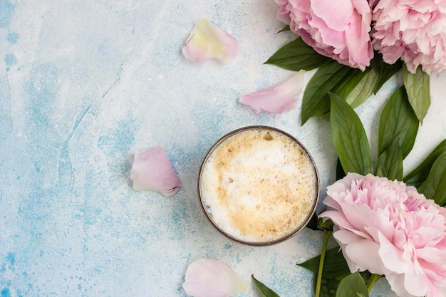 Cup of coffee or cappuccino and pink peonies
