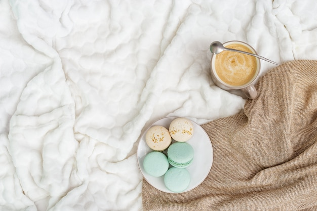 Cup coffee cappuccino and tasty sweet macaroons on light background with copy space. winter morning concept, time for relax. top view. flat lay