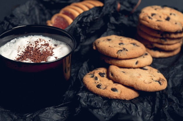 Cup of coffee, cappuccino with chocolate cookies and biscuits on black table.