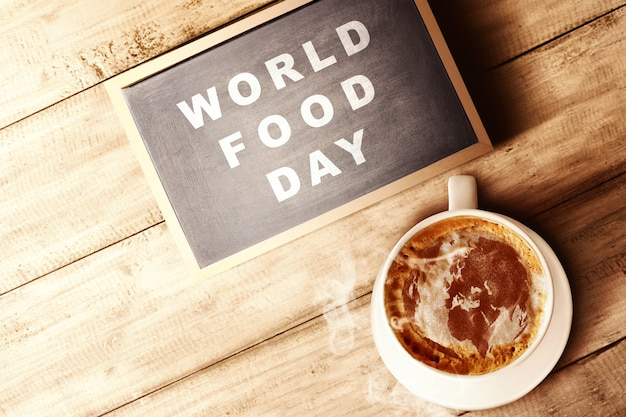 The cup of coffee and chalkboard with world food day text on wooden