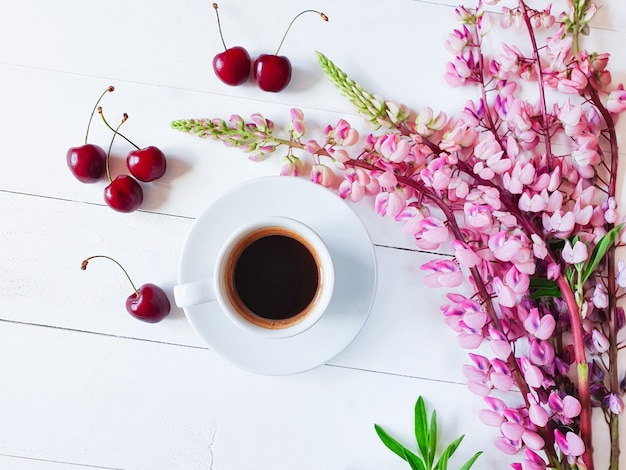 Cup of coffee, cherry berries on plank table painted white. top view, lifestyle.