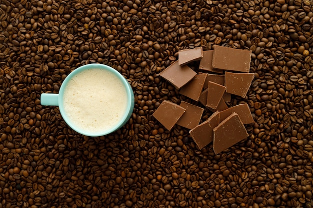 Cup of coffee and chocolate chips on a bed of coffee beans