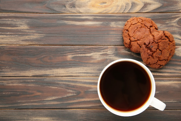 Cup of coffee and chocolate cookies on brown wooden table.