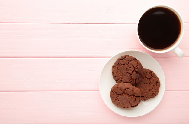 Cup of coffee and chocolate cookies on pink wooden table.