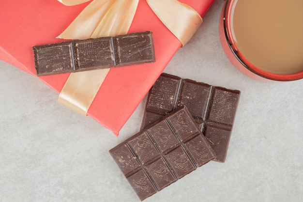 Cup of coffee, chocolate and gift box on marble surface