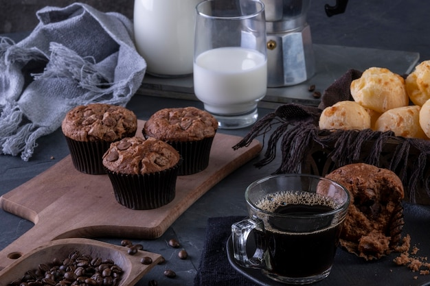 A cup of coffee, chocolate muffins, cheese breads and milk.