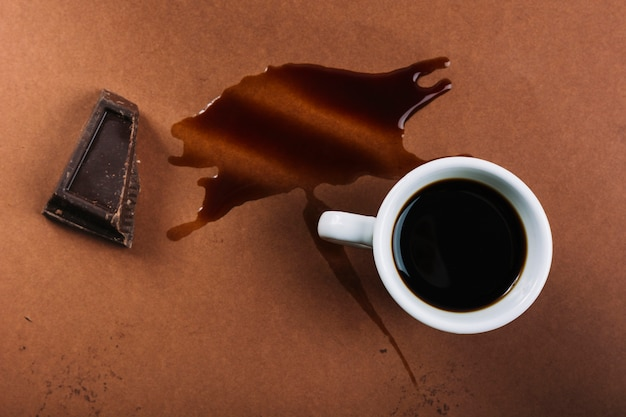 Cup of coffee and chocolate near splash of drink