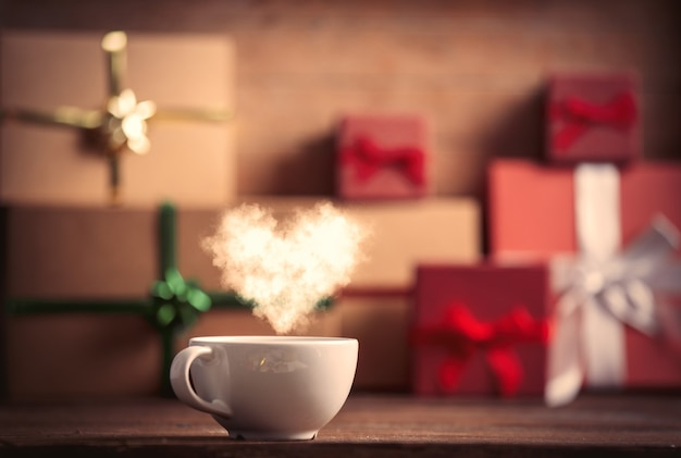 Cup of coffee and christmas gifts on background