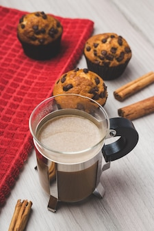Cup of coffee, cinnamon and muffins