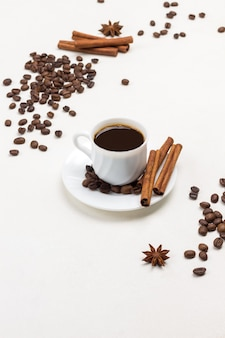 Cup of coffee, cinnamon sticks and star anise on saucer. grains of coffee and cinnamon on table. white background. top view