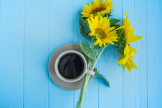 A cup of coffee cinnamon and sunflower on a blue background.