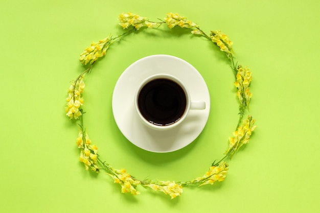 Cup of coffee and circular frame yellow wild flowers linaria on green background concept good morning or hello spring