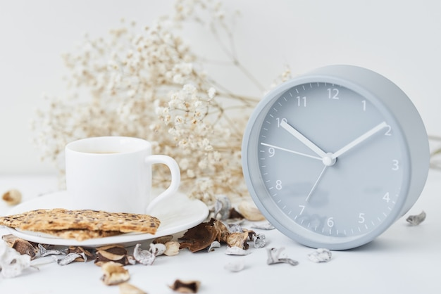 Cup of coffee and classic alarm clock on a white table.