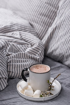 Cup of coffee or cocoa on the bed