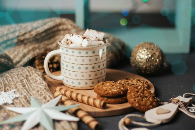 Cup of coffee or cocoa with marshmallows, cinnamon sticks, knitted plaid and christmas toys.
