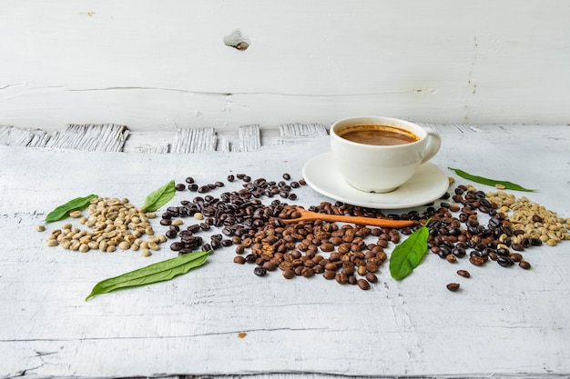 Cup of coffee and cofee bean on white wooden table