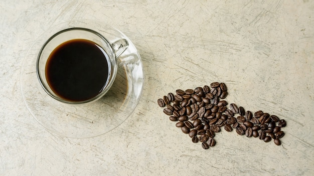 A cup of coffee and a coffee bean on a gray background.