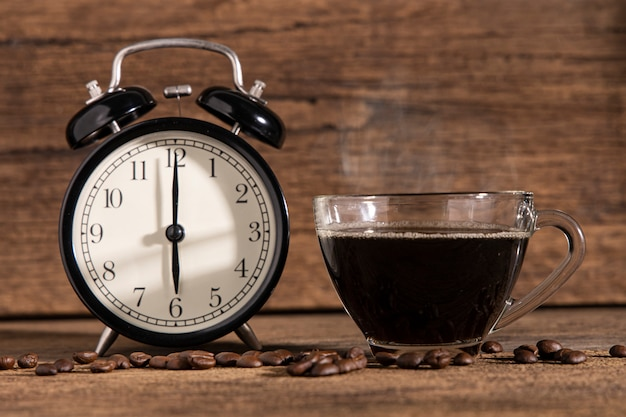 A cup of coffee and coffee bean with clock on wooden table wall.
