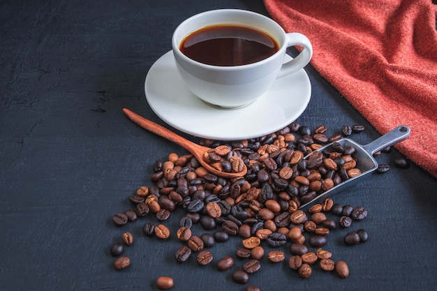Cup of coffee and coffee beans on black background