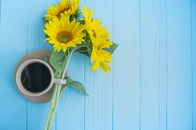 A cup of coffee, coffee beans, cinnamon and sunflower on blue