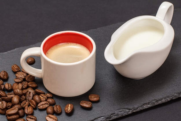 Cup of coffee, coffee beans and jug of cream on black background. top view.