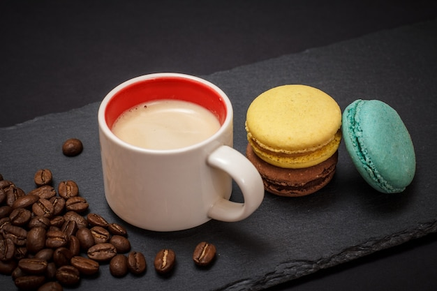 Cup of coffee, coffee beans and macaroons on black background. top view.