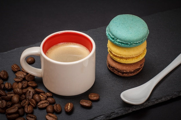 Cup of coffee, coffee beans, macaroons and spoon on black background. top view.