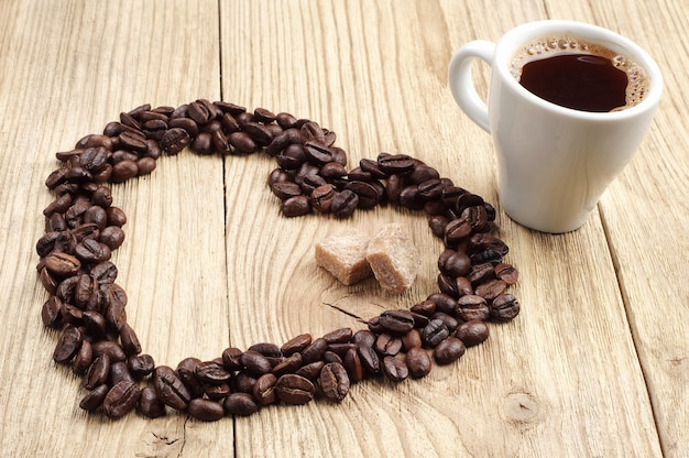 Cup of coffee and coffee beans the shape of hearts on wooden background