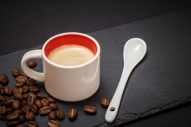 Cup of coffee, coffee beans and spoon on black background. top view.