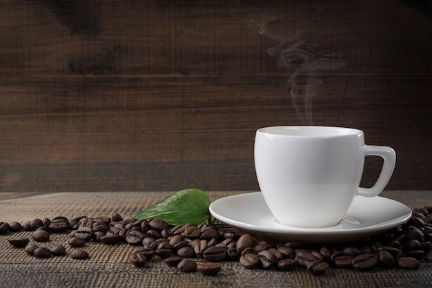 A cup of coffee and coffee beans on the table. black background