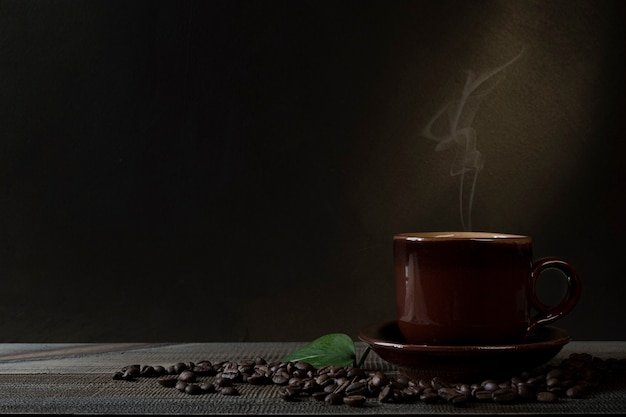 Cup of coffee and coffee beans on the table. dark background.