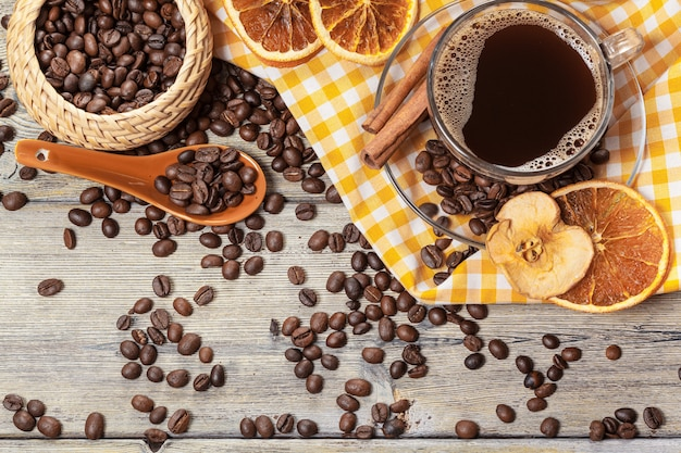 Cup of coffee and coffee beans on table.