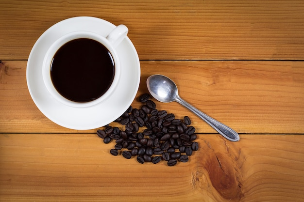 Cup of coffee and coffee beans on wood